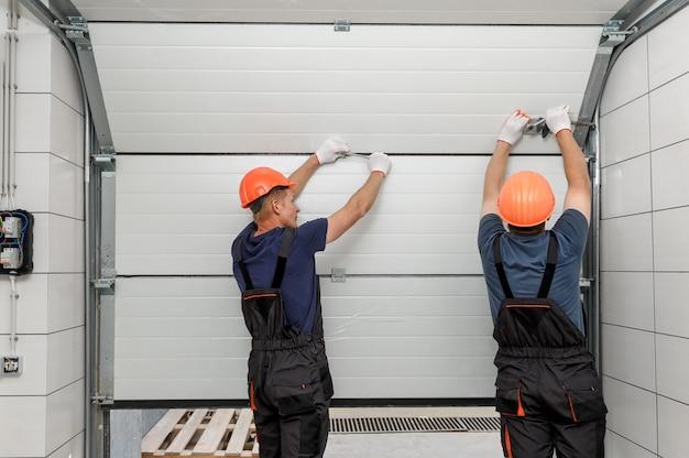Werknemers installeren hefpoorten van de garage.