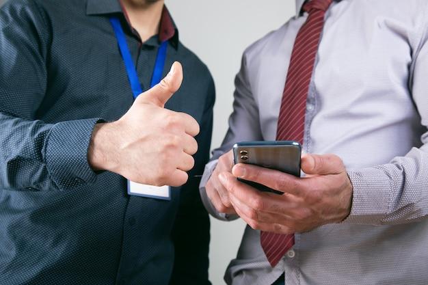 Werknemers kijken naar de telefoon en laten hun duimen zien.
