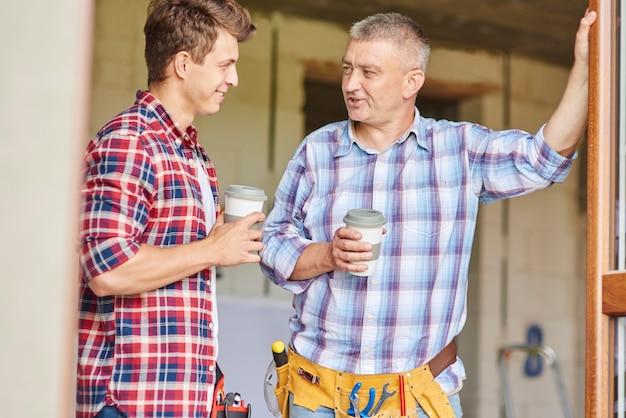 Werknemers maken een praatje terwijl ze een kopje koffie drinken