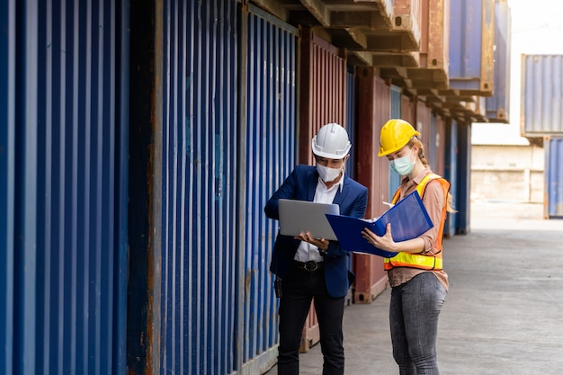 Werknemers met behulp van een laptop en het dragen van gezichtsmaskers