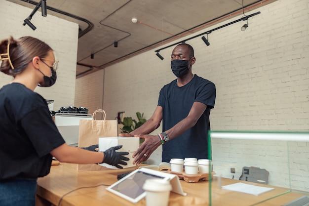 Werknemers met masker werken samen in pandemie
