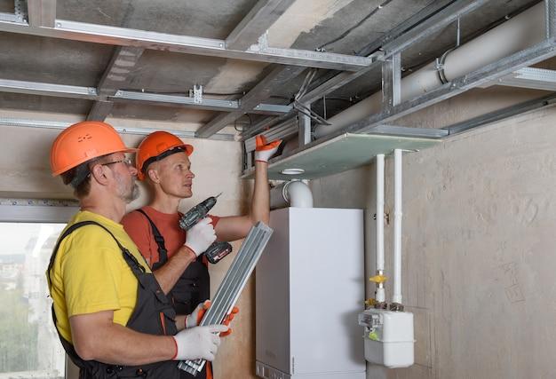 Werknemers monteren een complex frame voor gipsplaat aan het plafond.
