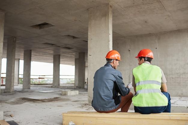 Werknemers op de bouwplaats achteraanzicht