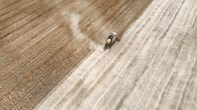 Werknemers op maaidorser verzamelen rijpe maïs. luchtfoto bovenaanzicht