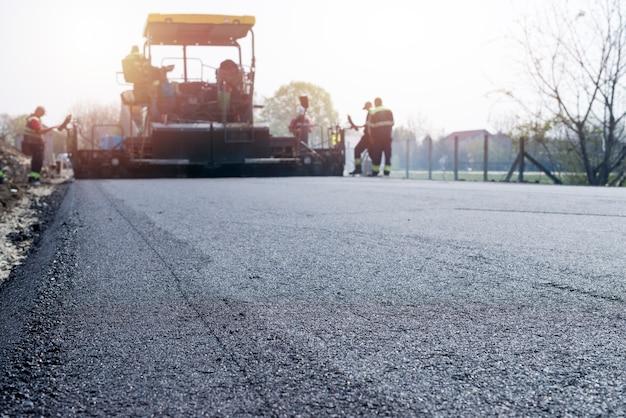 Werknemers plaatsen nieuwe asfaltlaag op de weg