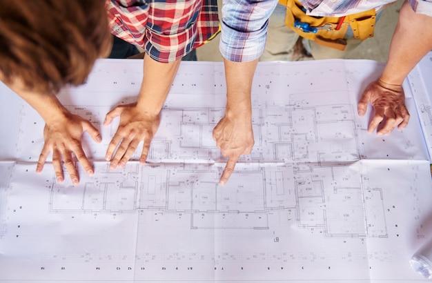 Werknemers praten over het bouwproject in het hoofdplan
