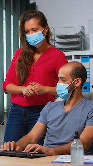 Werknemers praten tijdens het coronavirus met beschermende gezichtsmaskers in de kantoorruimte. team in nieuwe normale kantoorwerkruimte in persoonlijk zakelijk bedrijf typen op computertoetsenbord en wijzend op desktop