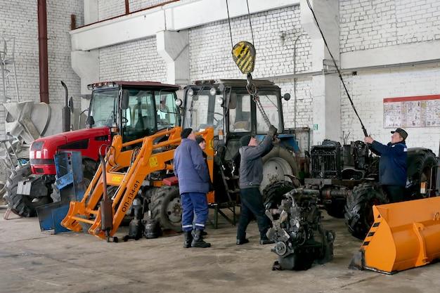 Werknemers repareren landbouwmachines vóór veldwerk