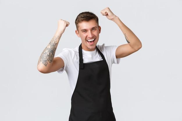 Werknemers, supermarkten en coffeeshopconcept. gelukkige knappe barista, mannelijke cafémedewerker of ober, viert opening, vuistpomp en zegt ja, triomfeert, voelt zich kampioen.