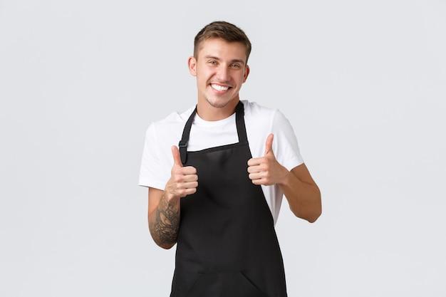 Werknemers, supermarkten en coffeeshopconcept. knappe vriendelijke kerel werknemer in café, winkelbediende met zwarte schort, duimen opdagen en glimlachen om gast te verwelkomen, kwaliteit garanderen