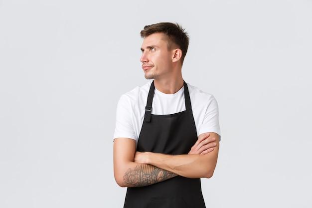 Werknemers, supermarkten en coffeeshopconcept. ontevreden knorrige barista, cafémedewerker in zwarte schort die zich boos of beledigd voelt, mokkend afwendt en de armen oversteekt, witte achtergrond