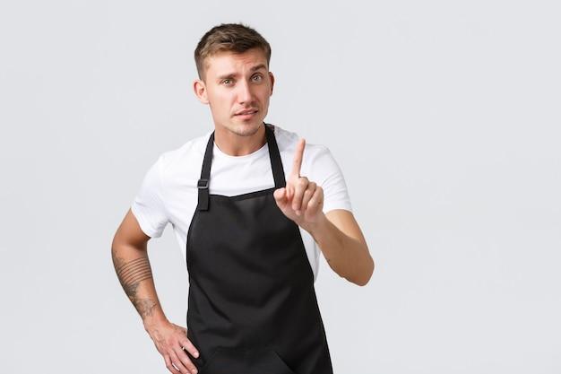 Werknemers, supermarkten en coffeeshopconcept. serieus ogende knappe barista die les geeft over hoe je koffie thuis zet, vinger schudt als uitbrander, iets verbiedt of verbiedt