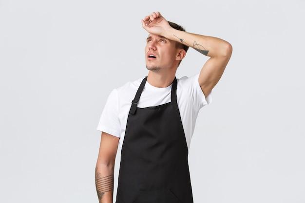 Werknemers, supermarkten en coffeeshopconcept. vermoeide ober die opkijkt en uitademt van vermoeidheid, barista veegt zweet van het voorhoofd, moet pauzeren, uitgeput voelen serveertafels, witte achtergrond