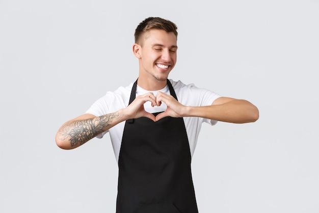 Werknemers, supermarkten en coffeeshopconcept. vrolijke knappe ober die gasten uitnodigt om een nieuw café of restaurant te bezoeken, een hartteken te tonen en te lachen met gesloten ogen, witte achtergrond