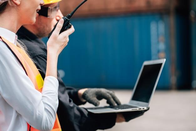 Werknemers teamwerk man en vrouw in veiligheid jumpsuit werkkleding met gele veiligheidshelm en laptop controleren container bij vracht verzending magazijn.