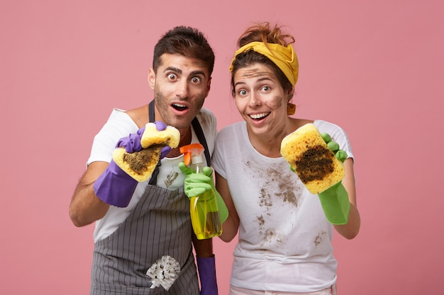 Werknemers van de dienstreiniging die stof met sponzen wegvegen. gelukkig huisvrouwen huis schoonmaken met wasmiddel en haar man met verbaasde uitdrukking