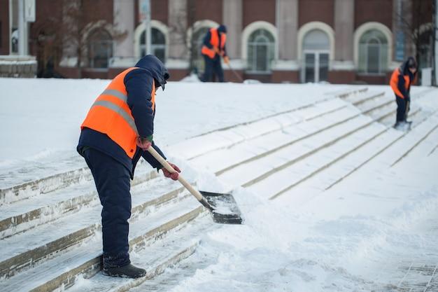 Werknemers vegen in de winter sneeuw van de weg.