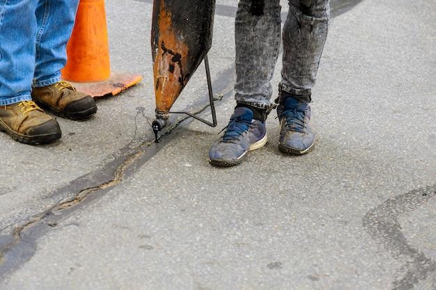 Werknemers voeren kleine reparaties aan bestrating uit door vloeibaar asfalt in putten op wegen die scheuren in de wegenbouw afdichten