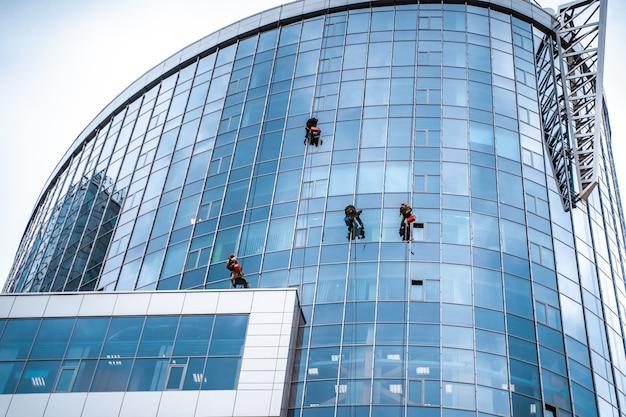 Werknemers wassen van ramen in het kantoorgebouw