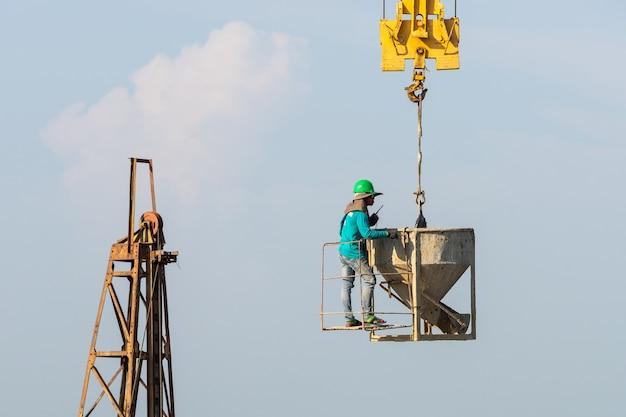 Werknemers werken op de kraan in de bouwplaats
