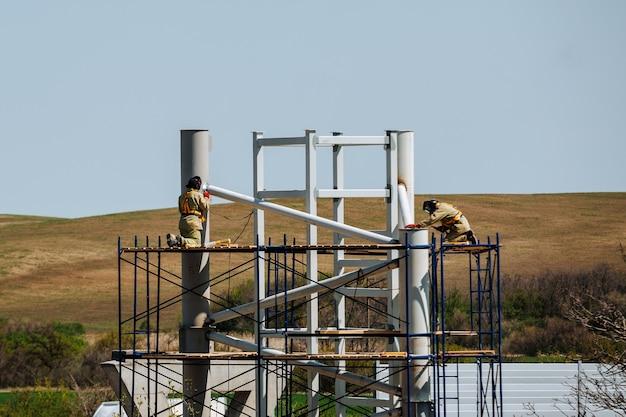 Werknemers werken op een bouwplaats terwijl ze op steigers staan. werknemers lassen. metalen constructie.