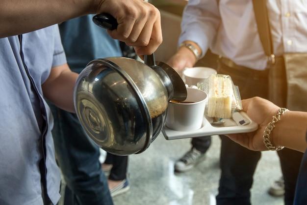 Werknemers worden koffiepauze geserveerd tussen vergadering en snack op schotel, koffieconcept.
