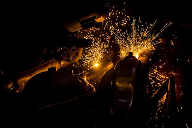 Werknemers zijn groeven met koolstof lasdraden met vonken