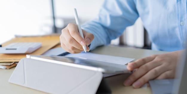 Werknemershand met styluspen om op het tabletscherm te wijzen om de bedrijfswinst maandelijks te tonen