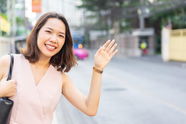 Werknemersvrouw die hand opheffen om taxi-auto togo op te roepen om in de spits te werken