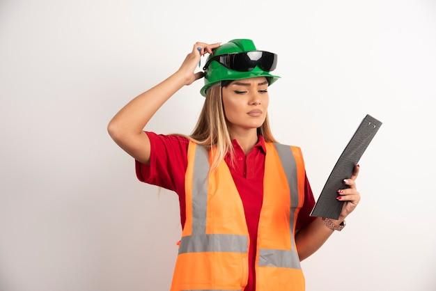 Werknemersvrouwenindustrie in vest op zoek op klembord