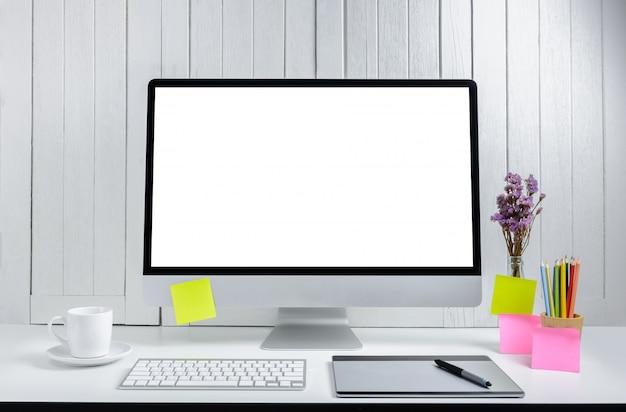Werkplaatsachtergrond voor ontwerpers met de lege witte het scherm moderne bureaucomputer.