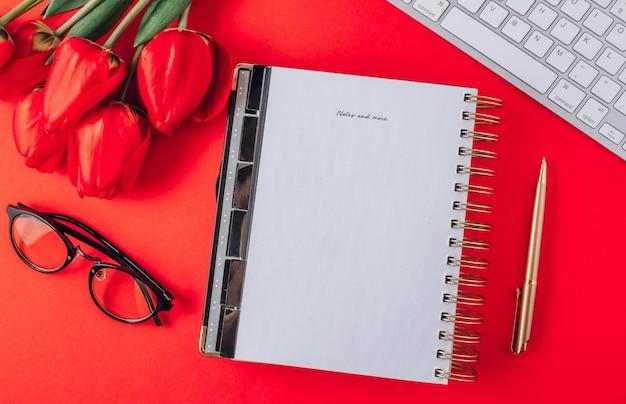 Werkplek aan huis: leeg notitieboekje, bril, toetsenbord, tulpenbloemen