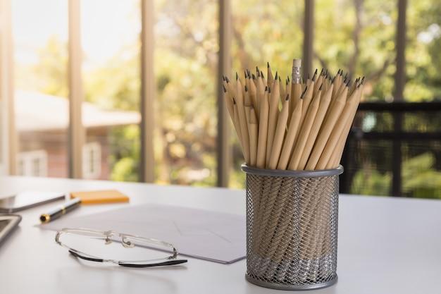 Werkplek concept. sluit omhoog van potloden in stanless geval op bureau met lezingsglazen, documentdocument