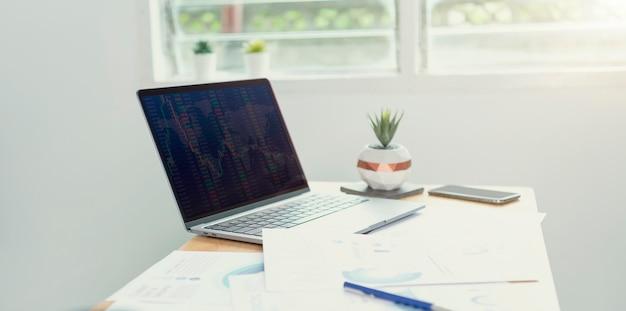 Werkplek desktop computer laptop voor het maken van forex trading aandelenfinanciën en boekhouding analyseer financiële in kantoorruimte.