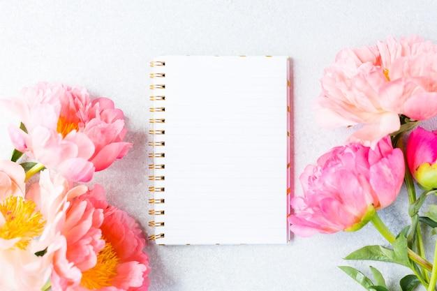 Werkplek, desktopweergave. roze pioenroos en leeg notitieboekje op wit