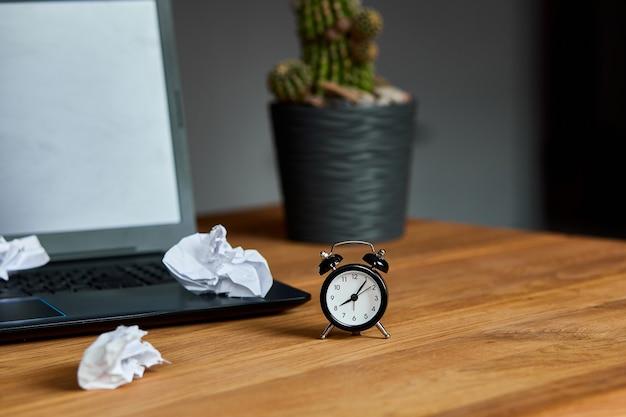 Werkplek, houten bureau met klok, vel papier, laptop, notitieboekje, verfrommeld papier