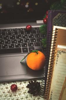 Werkplek in de winter, achtergrond van laptop met voedsel citrus mandarijnen en boeken, blocnotes op gebreide wollen trui. hoge kwaliteit foto