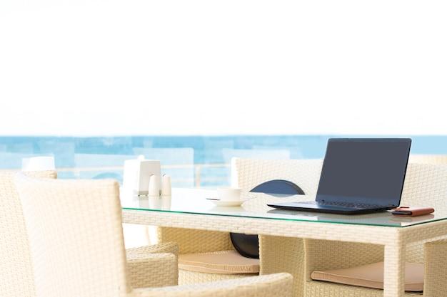Werkplek in een café met uitzicht op zee. man aan het werk op een laptop in een café. kopieer ruimte. bespotten.