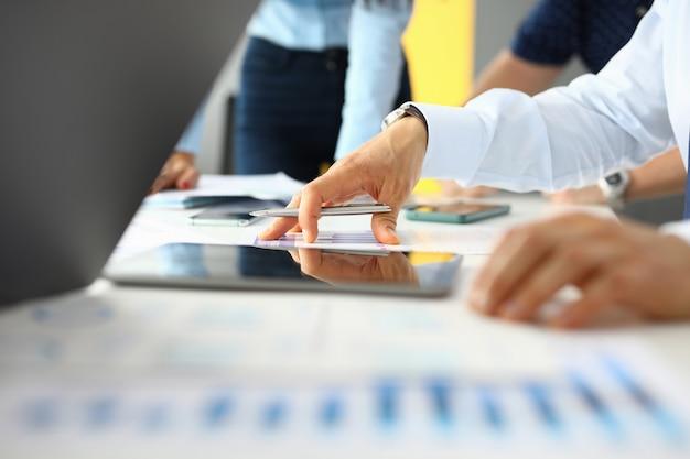 Werkplek in kantoor op tafel zijn tabletdocumenten, collega's houden pennen in hun handen.