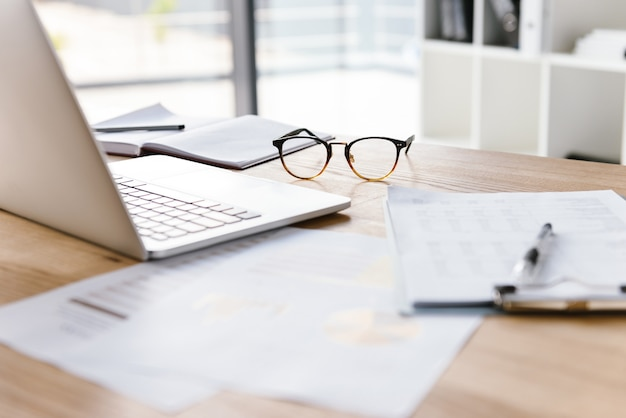Werkplek in kantoorruimte zonder mensen met opengeklapte laptop, klembord, bril, potlood en notitieboekje liggend op houten bureau