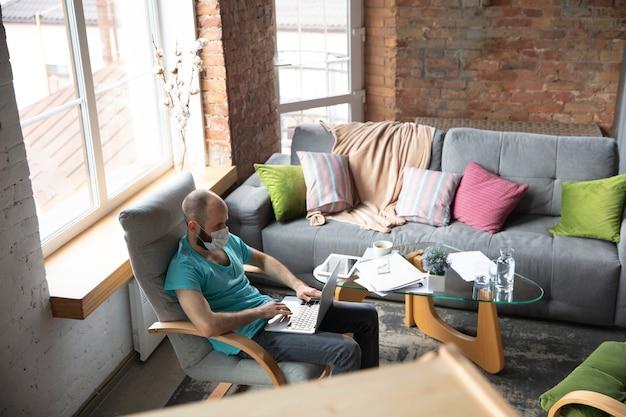 Werkplek. jonge man die thuis yoga doet terwijl hij in quarantaine zit en freelance online werkt. extern kantoor, geïsoleerd. concept van gezonde levensstijl, wellness, veilig zijn tijdens een pandemie van het coronavirus.