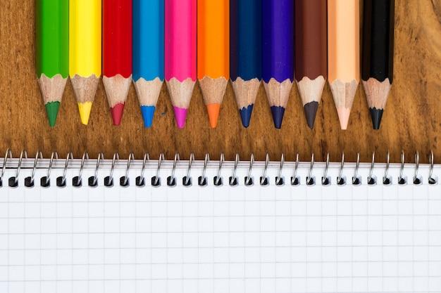 Werkplek. kladblok en kleurrijke potloden