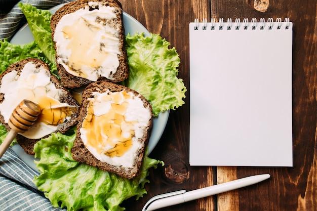 Werkplek met blanco notitieboek, pen en broodjes