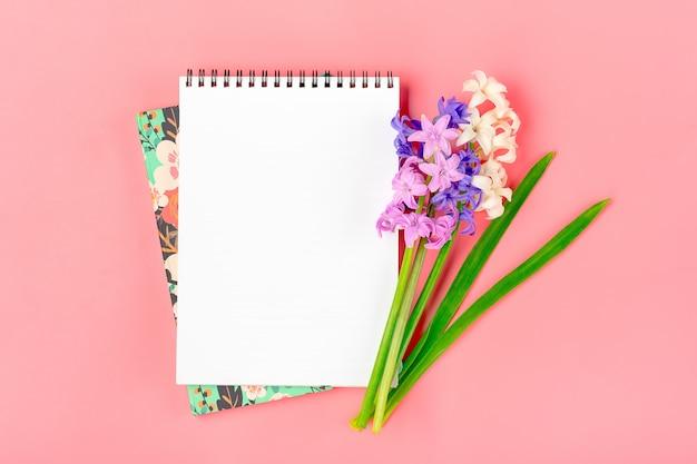 Werkplek met boeket van hyacinten bloemen, witte notitieblok op roze achtergrond plat lag bovenaanzicht mock up