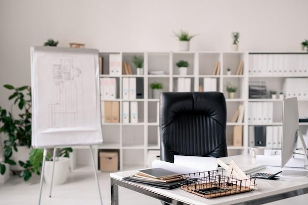 Werkplek met bureau, zwart lederen fauteuil, whiteboard, computermonitor en andere benodigdheden op de achtergrond van planken met documenten