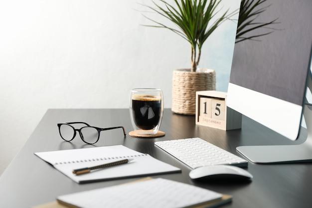 Werkplek met computer, bril en kalender op zwarte houten tafel, kopie ruimte