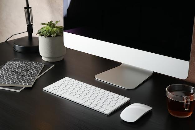 Werkplek met computer, kopje thee en plant op zwarte houten tafel