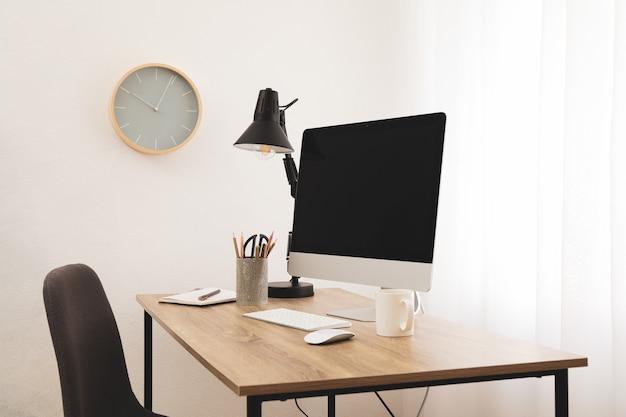 Werkplek met computer, stoel en kopje koffie op houten tafel. klok op de muur