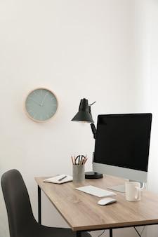Werkplek met computer, stoel en kopje koffie op houten tafel, kopie ruimte
