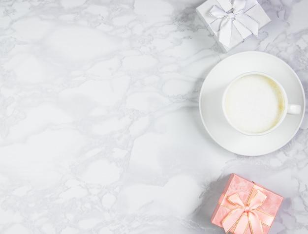 Werkplek met een kopje koffie en geschenkdozen op een marmeren tafel. bovenaanzicht, plat lag, kopie ruimte